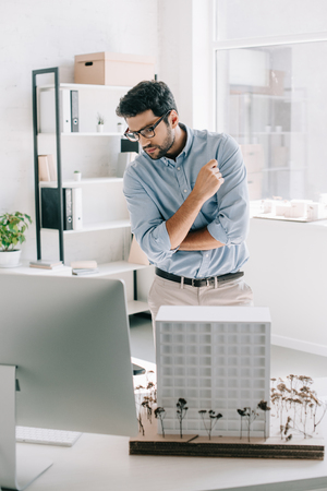 Foto de handsome architect looking at computer near architecture model on table in office - Imagen libre de derechos