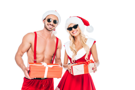 Photo pour portrait of young couple in christmas hats and sunglasses holding gift boxes isolated on white background - image libre de droit