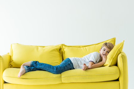 Photo pour adorable boy lying in casual clothes on yellow sofa isolated on white - image libre de droit