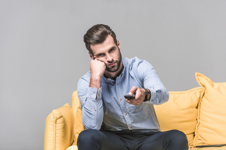 Photo pour handsome bored man with remote control watching TV on yellow sofa on grey - image libre de droit