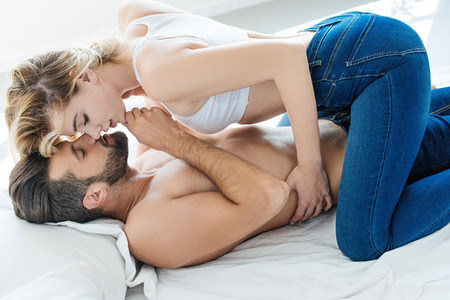Photo pour side view of beautiful sexy young couple kissing on bed - image libre de droit