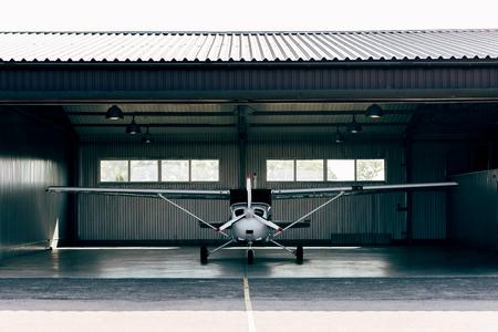 Foto de small modern white airplane standing in hangar - Imagen libre de derechos