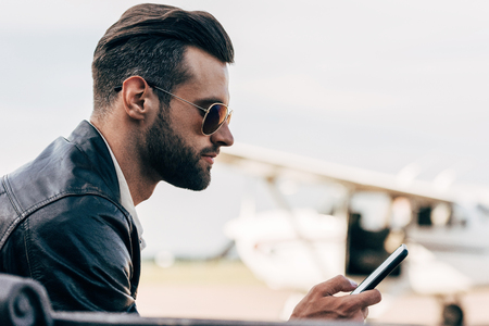 Photo pour side view of stylish man in leather jacket and sunglasses using smartphone - image libre de droit