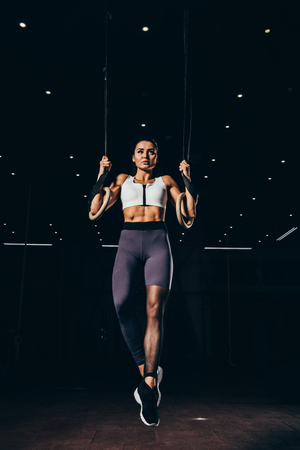 Photo pour attractive sporty woman exercising with gymnastic rings - image libre de droit