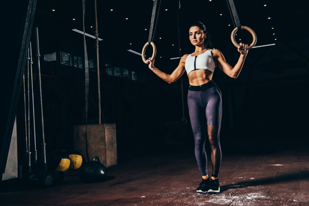Photo pour attractive sporty woman working out with gymnastic rings - image libre de droit