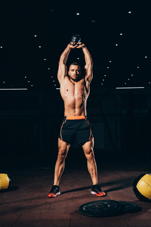 Photo pour handsome muscular man holding kettlebell overhead while working out  in dark gym - image libre de droit