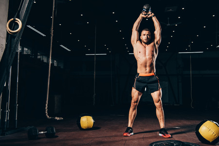 Photo pour handsome athletic man holding kettlebell overhead while working out  in dark gym - image libre de droit