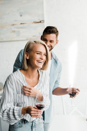 Photo pour young couple holding glasses of wine and laughing in kitchen - image libre de droit