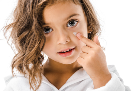 Photo pour Portrait of little kid applying on facial cream isolated on white background - image libre de droit