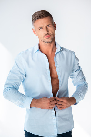 Photo pour Sexy macho buttoning shirt and looking at camera isolated on white background - image libre de droit