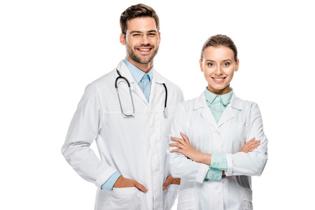 Photo pour Handsome happy male doctor standing near female colleague with crossed arms isolated on white background - image libre de droit