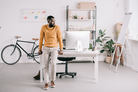 Photo for Handsome African American designer in orange sweater leaning on table and looking away in office - Royalty Free Image