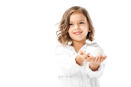 Photo pour Cute kid in white bathrobe showing body cream in hands isolated on white background - image libre de droit