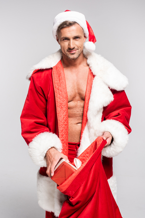 Foto de Sexy man in Santa costume opening red bag and smiling at camera isolated on grey background - Imagen libre de derechos