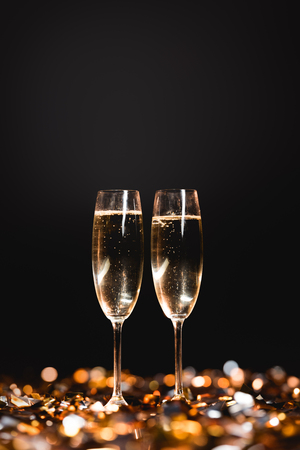 Photo for New year celebration with champagne glasses on golden confetti on black - Royalty Free Image