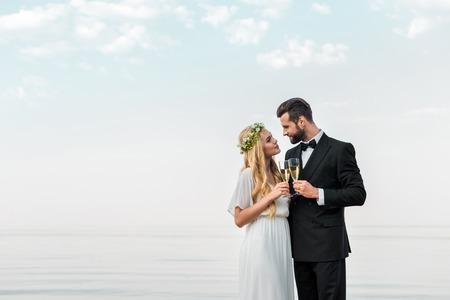Foto de Affectionate wedding couple clinking with glasses of champagne on beach - Imagen libre de derechos