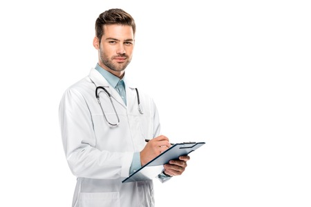 Foto de Happy male doctor with stethoscope over neck writing in clipboard isolated on white background - Imagen libre de derechos