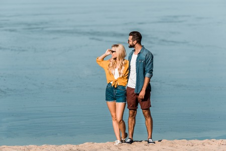 Photo pour Couple in casual clothes looking away on beach - image libre de droit