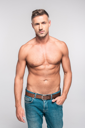 Photo pour Portrait of handsome bare-chested man in jeans looking at camera isolated on grey background - image libre de droit