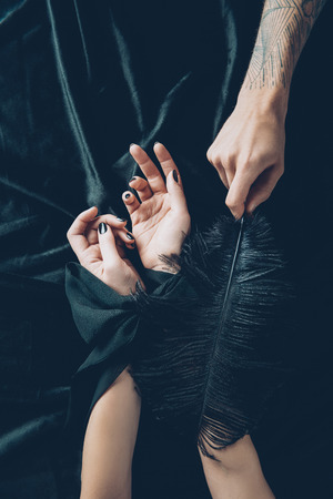 Photo for cropped shot of woman with tied hands and man holding black feather - Royalty Free Image