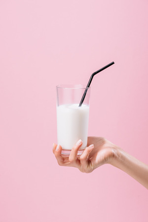 Foto de cropped shot of woman holding glass of milk isolated on pink - Imagen libre de derechos