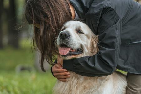 Photo pour young woman hugging cute funny dog in park - image libre de droit
