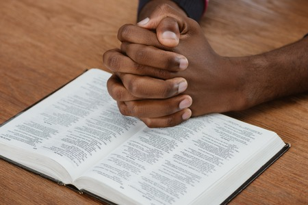 Photo for cropped shot of african american man praying with holy bible on wooden table - Royalty Free Image
