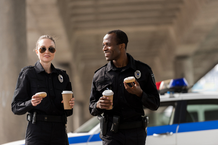 Photo pour smiling police officers having coffee break with doughnuts - image libre de droit