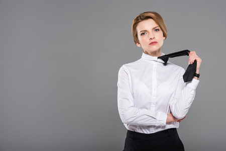 Photo pour beautiful serious businesswoman in tie, isolated on grey - image libre de droit