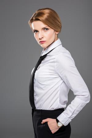 Foto de serious businesswoman in white shirt and tie, isolated on grey - Imagen libre de derechos