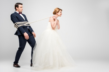 Foto de bride in wedding dress pulling groom bound with rope, isolated on grey, feminism concept - Imagen libre de derechos