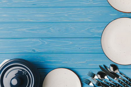 Photo for top view of plates, utensil and pan on blue table - Royalty Free Image