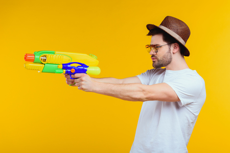 Foto de Side view of young man holding water gun and looking away isolated on yellow background - Imagen libre de derechos