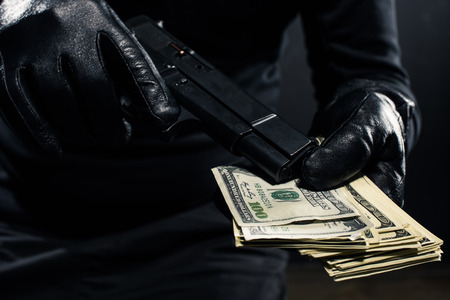 Foto de Close-up view of gun and dollars in hands of robber - Imagen libre de derechos