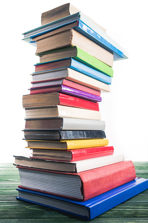 Photo for High bent tower of stacked books on wooden table - Royalty Free Image