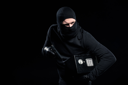Foto de Burglar in balaclava holding gun and locked safe box - Imagen libre de derechos
