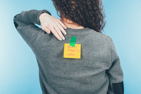 Foto de Back view of woman with note on sticky tape with April fools day lettering on back, April fools day concept - Imagen libre de derechos