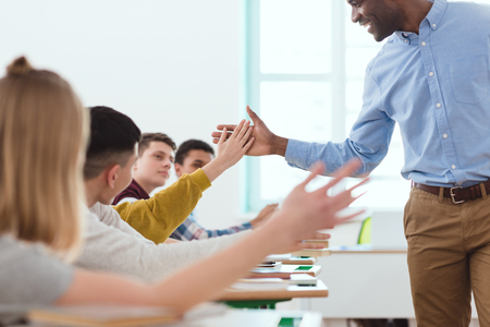 Photo for Cropped image of African American taking high five to multicultural high school teenage students - Royalty Free Image