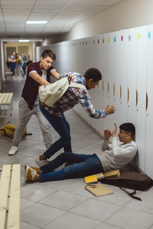Photo pour Asian and African American schoolboys being bullied in school corridor by their classmate - image libre de droit