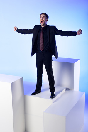 Foto de Businessman in black suit with outstretched arms standing on white block isolated on blue background - Imagen libre de derechos
