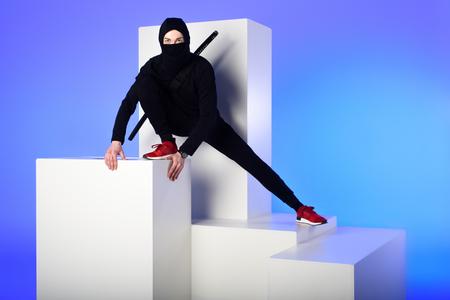 Photo for Ninja in black clothing with katana behind on white block isolated on blue background - Royalty Free Image