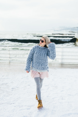 Photo for Stylish young girl in sunglasses and light blue merino sweater on winter quay - Royalty Free Image