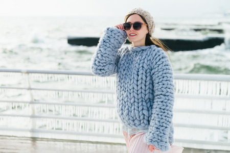 Photo for Stylish young girl in sunglasses and merino wool sweater on winter quay - Royalty Free Image