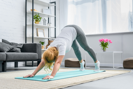 Foto de Woman in downward facing dog position on yoga mat - Imagen libre de derechos