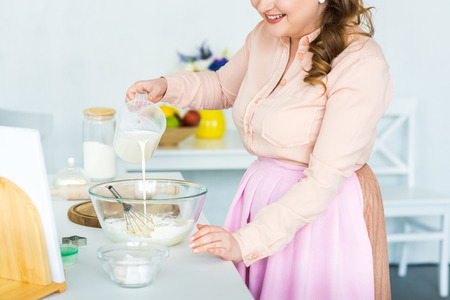 Photo for Cropped image of woman pouring milk into bowl with flour at kitchen - Royalty Free Image