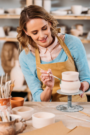 Photo pour Beautiful potter painting ceramic jug in workshop - image libre de droit