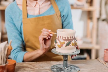 Photo pour Partial view of potter in apron painting traditional ceramic jug - image libre de droit