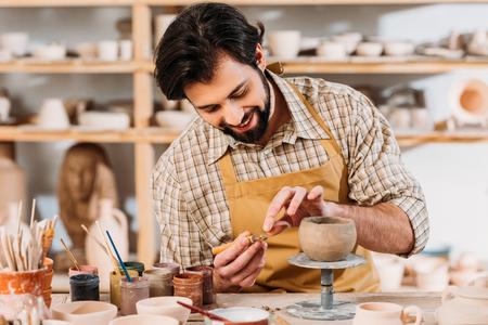 Photo pour Happy potter in apron decorating ceramic bowl in workshop - image libre de droit