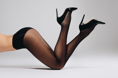Foto de Slim woman in black pantyhose lying on white background - Imagen libre de derechos