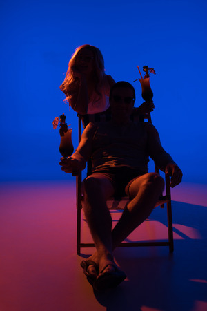 Foto de Silhouette of woman leaning on chair with man and holding cocktails on blue background in dark light - Imagen libre de derechos